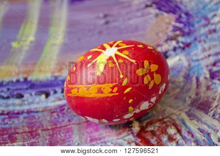 Single easter egg with beautiful color abstract pattern isolated on colored textured background.