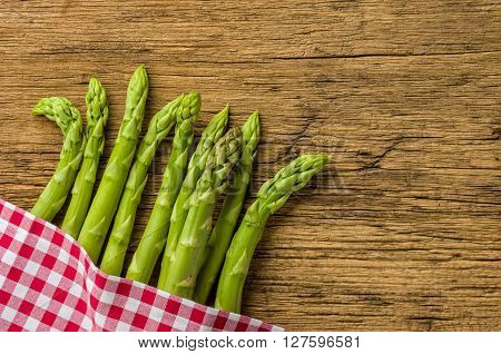 Green Asparagus On A Wooden Board With A Checkered Tablecloth