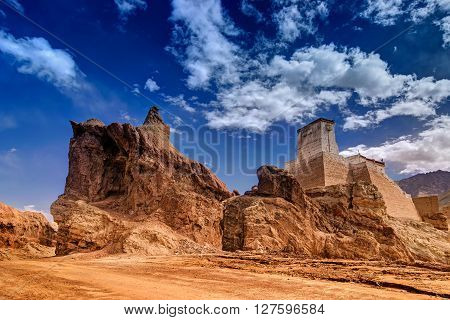 Ruins and Basgo Monastery surrounded with stones and rocks Blue sky with clouds in the background Himalayan Mountain range Leh Ladakh Jammu and Kashmir India