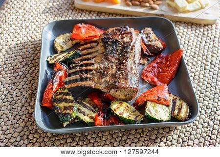 Grilled rack of lamb chops with grilled vegetables and rosemary on a sunny day.