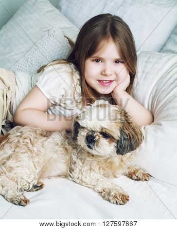 happy girl with her dog in bed at home
