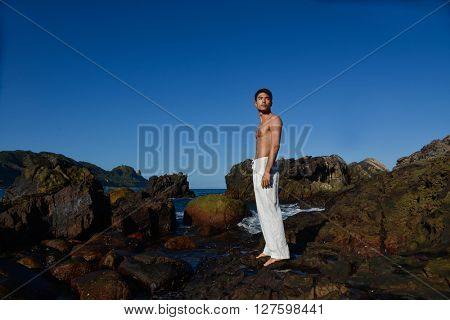 Full body healthy muscular Yoga man in the morning at beach