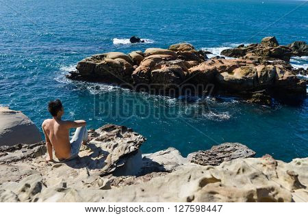 Young sport man sitting back on rocks at beach