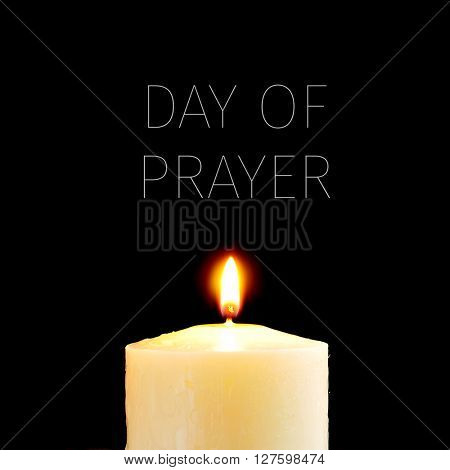 a lit candle and the text day of prayer written in white against a black background