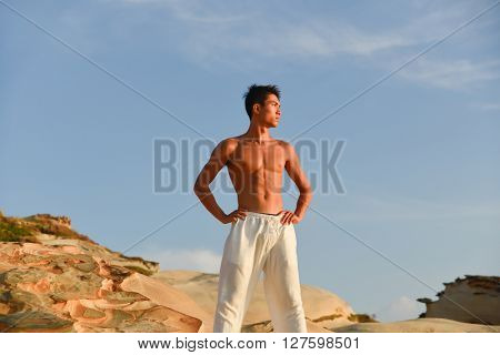 male model with muscles in exercise outdoors. over mountain