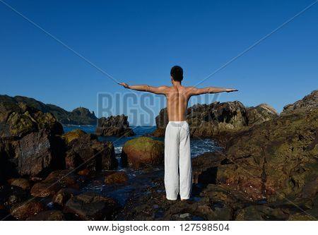 full body back handsome man doing yoga exercise in outdoors