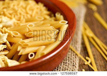Closeup of an earthenware bowl with different uncooked pasta such as ravioli, spaghetti or mostaccioli, on a rustic wooden table