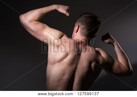Muscular man shows his biceps back. Athletic man on a dark background