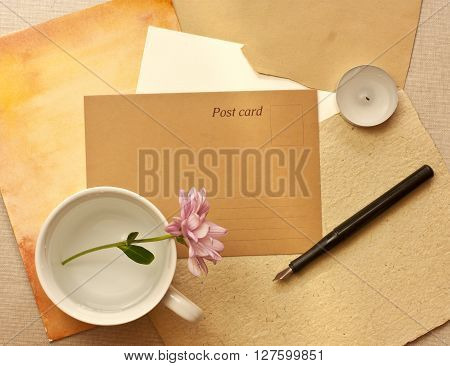 A vintage style still life with a brown paper postcard with a place for text a tender pink chrysanthemum in a white cup an ink pen a candle and some old paper textures
