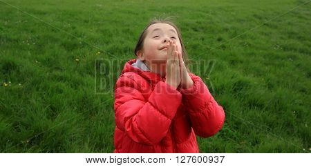 Portrait of beautiful girl praying in the park