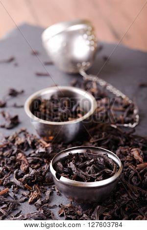 Tea Strainer Full Of Dry Tea Leaves On Black Stone