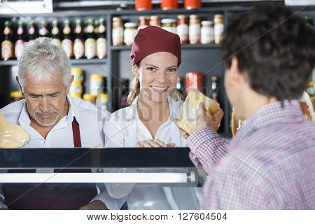 Smiling Saleswoman Serving Cheese To Customer In Shop
