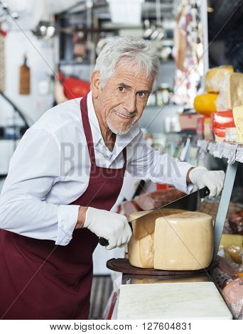 Happy Salesman Slicing Whole Cheese With Knife In Shop