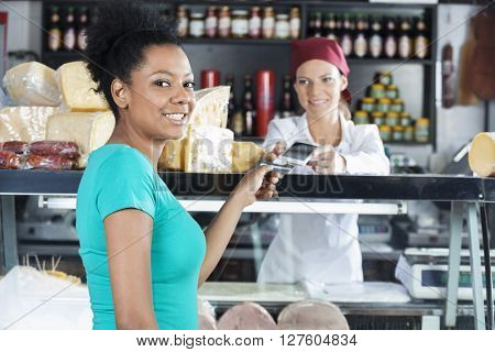 Woman Making Payment To Saleswoman In Cheese Shop