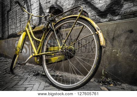 Vintage yellow bike standing against a wall in a grungy alley