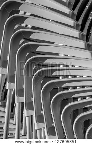 Abstract looking pile of stacked white plastic chairs
