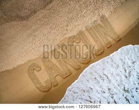 Cancun written on the beach