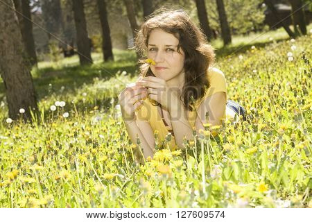 Young European woman with brown hair lay on meadow with yellow dandelions.