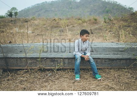 scared and alone, young  Asian child sitting