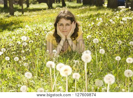 Young woman lays on meadow with white dandelions.
