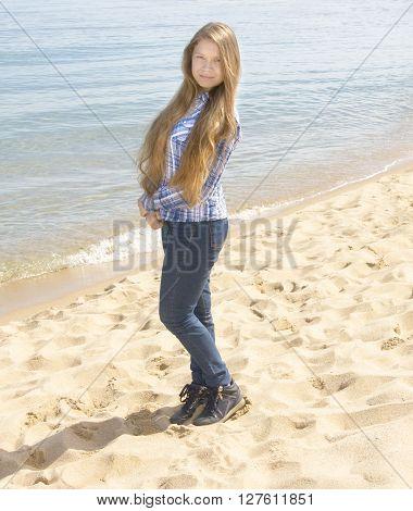 Young beautiful girl European long brown hair standing on sea beach.