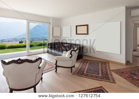 Interiors of new apartment, wide living room with white armchairs and many paintings on the wall