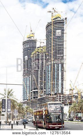 DubaiUAE - April 4 2016 : Cityscape of Dubai. Three skyscrapers under construction in foreground a touristic bus.