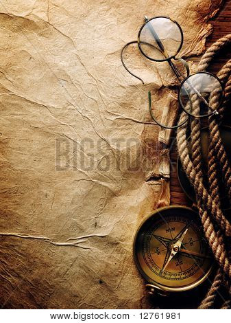 Compass, rope and glasses on old paper