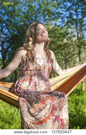 Portrait of Happy Smiling Blond Female Resting in Hummock in Spring Forest Outdoors.Vertical Image