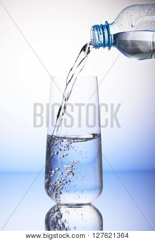 Water Pouring From Plastic Bottle In Half-filled Drinking Glass