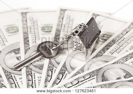 key with keychain in the form of a silver-colored house on a banknotes background
