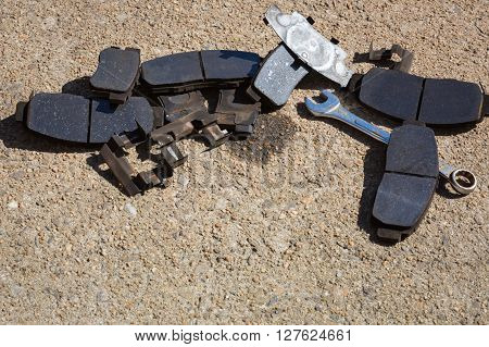 Worn used Brake Pads and tools on concrete