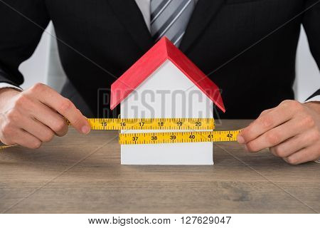 Businessman Hand Measuring House Model