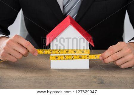 Businessman Hand Measuring House Model