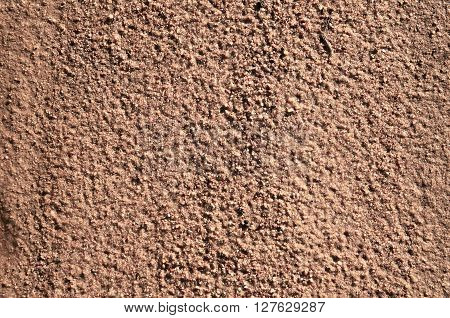 A background texture of unrefined damp and grainy natural golden sand.