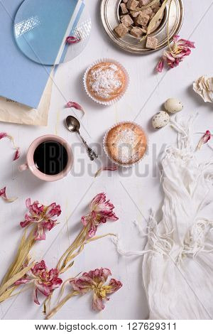 Coffee cup, cupcakes with pink tulip flowers and book on white rustic table from above, breakfast on Mothers day or Women's day.