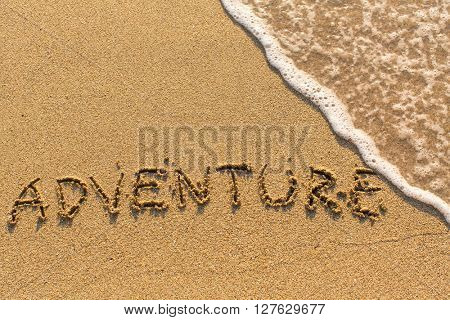 Adventure -  written on sandy beach with the soft wave.