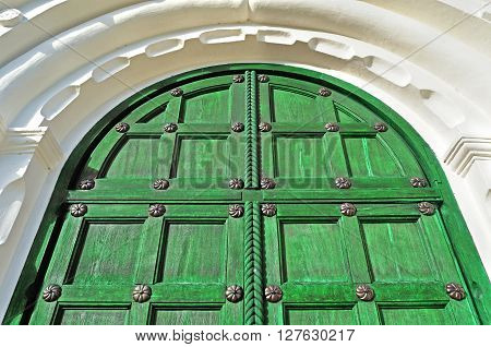 Architecture texture background. Vintage wooden bright green door with metallic rivets and upper arch of white stone - colored architecture background