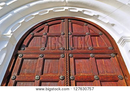 Architecture detailed background - aged wooden door of mahogany color with metal rivets and upper arch of white stone - vintage architecture background