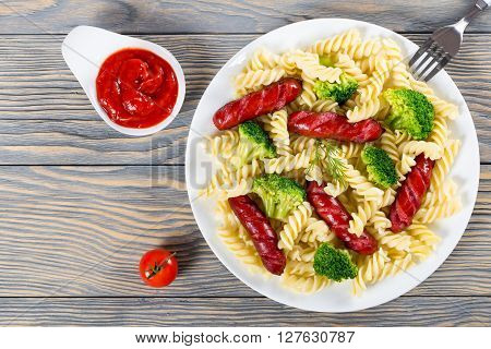 Delicious Spiral Pasta salad with broccoli and grilled sausages decorated with dill on a white dish with tomato sauce in a gravy boat studio lights top view