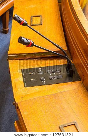 Two microphones for speaking in a council chamber.