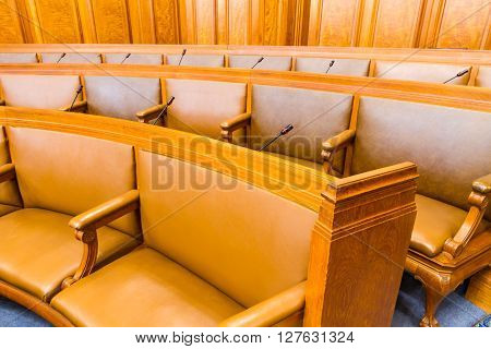 Wood and leather seats in a council chamber. Wood and leather upholstered.