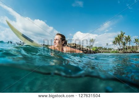 Young lady paddling on the surf board. Underwater split shot