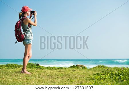 Young lady with rucksack taking a picture of the sea standing on the green glage
