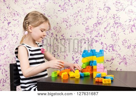 Little Girl Builds Bricks At Table