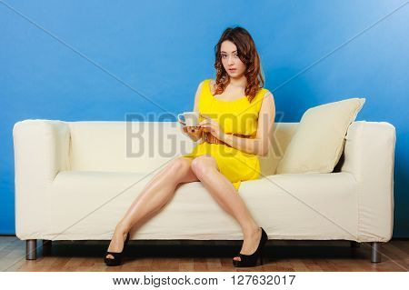 Beauty fashion and relax concept. Fashionable girl yellow dress holding hot drink coffee or tea cup sitting on sofa