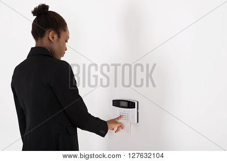 Businesswoman Entering Code In Security System