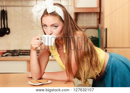 Pretty pin up girl with heart shape gingerbread cookies drinking tea or coffee at home. Gorgeous young retro woman with hot beverage relaxing in kitchen.