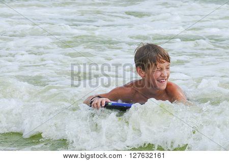 Happy cute kid on a boogie board in the ocean water with copy space.