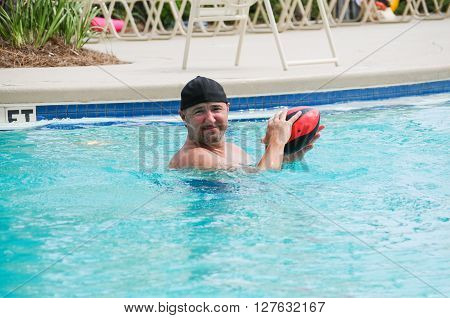Middle aged handsome man holding football in swimming pool.
